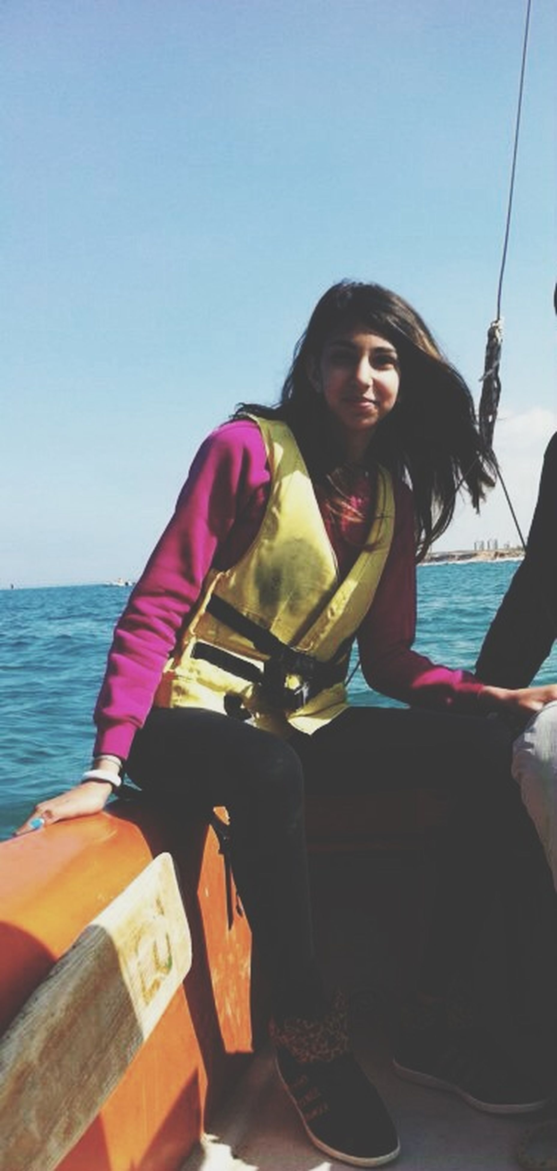 young adult, lifestyles, young women, person, leisure activity, casual clothing, long hair, clear sky, portrait, looking at camera, sea, water, sitting, sunglasses, three quarter length, front view, smiling