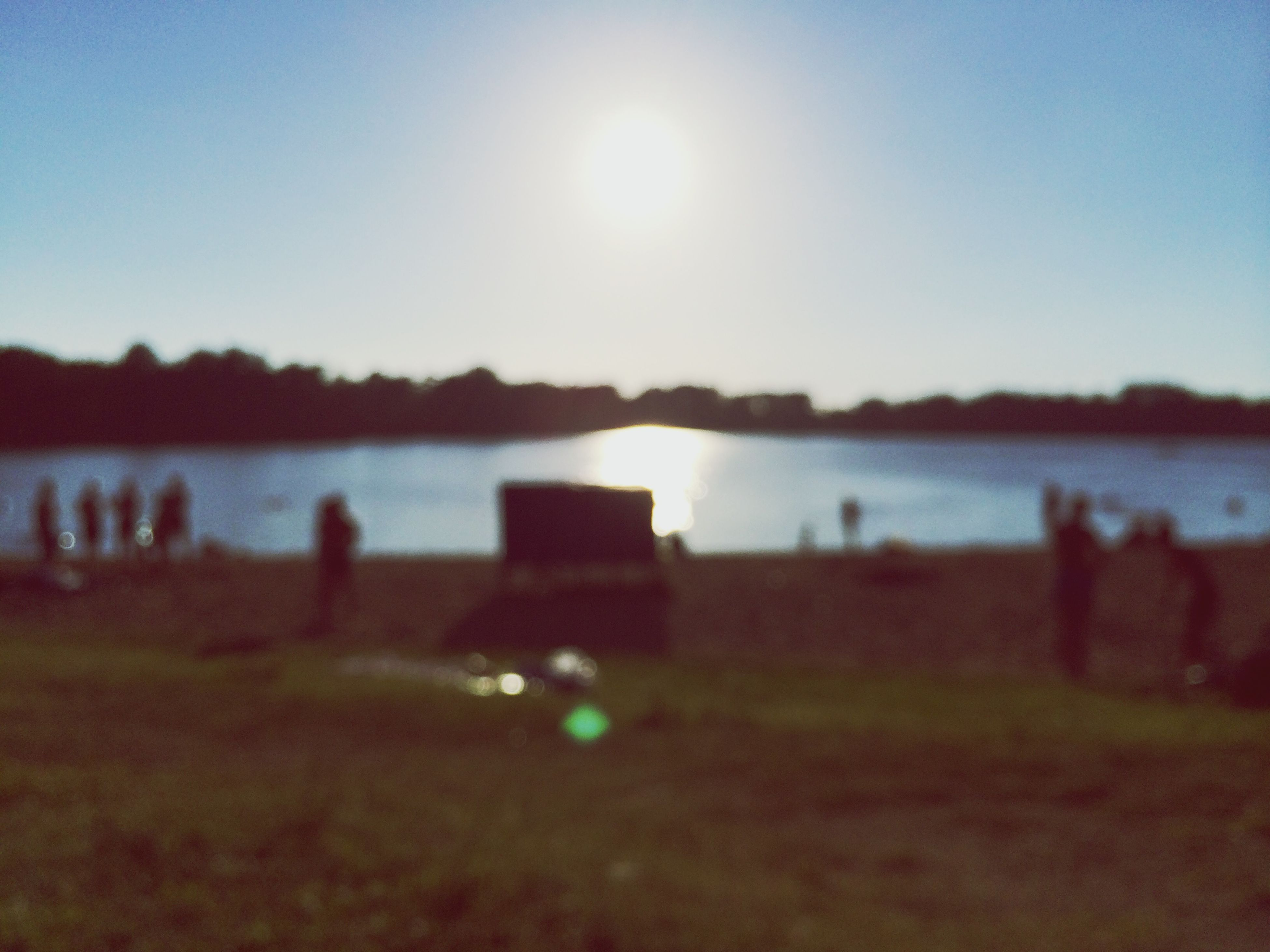 water, sun, clear sky, tranquil scene, tranquility, reflection, sunset, scenics, lens flare, lake, sunlight, beauty in nature, nature, sea, river, sky, idyllic, focus on foreground, outdoors, grass
