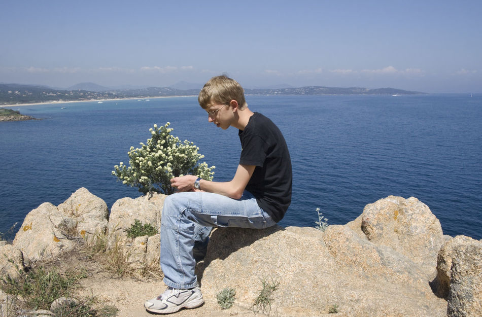 teen sitting on rocks - gulf of saint-tropez, French Riviera Adolescence  Casual Clothing Caucasian Cool Côte D'Azur France Full Length Kid One Boy Only One Teenage Boy Only Portrait Proile Rock Rocky Coastline Saint-Tropez Sea Serious Side View Sitting Teen Teenage Boy Teenager Thinking Thinking About Life Vacations