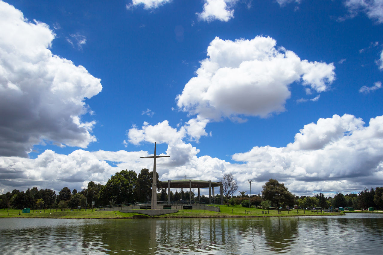 "Landscape view of lake at ""Simon Bolivar"" central park. Architecture Beauty In Nature Building Exterior Built Structure Catholic Central Park Cloud - Sky Cross Day Forest Green Color Lake Landscape Nature Nature No People Outdoors Park Simon Bolivar Park Sky Tree Water Water Reflections"