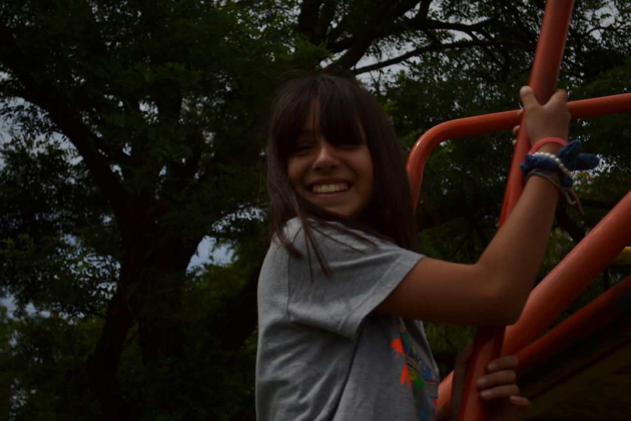 Adult Bangs Child Childhood Children Only Day Enjoyment Fun Leisure Activity Low Angle View One Girl Only One Person Outdoors People Playing Smiling Tree Young Adult