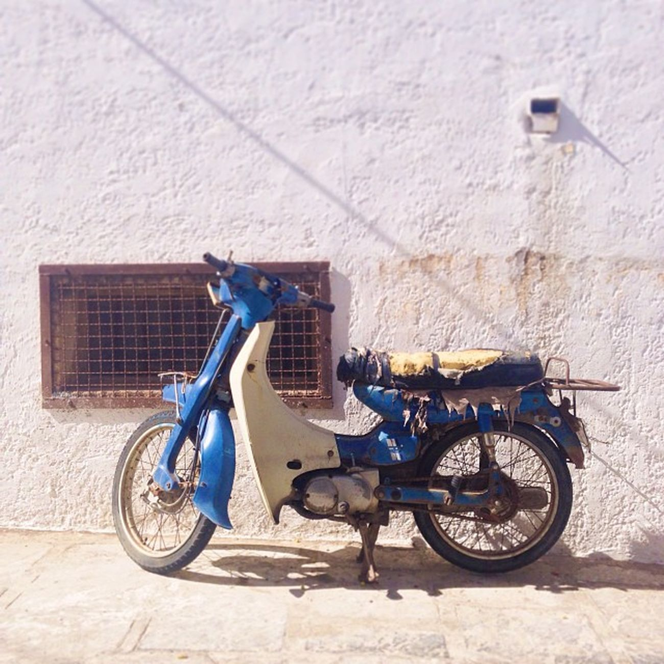 Comfortable Ride Ride Street Metal Streetart Foam Bike Rough Leather Comfortable Scooter Seat Wall Grate Stone Lindos Concrete Grill White Pictapgo Knackered Whitewash Greece Pictapgoapp Europe Sunny Comfy