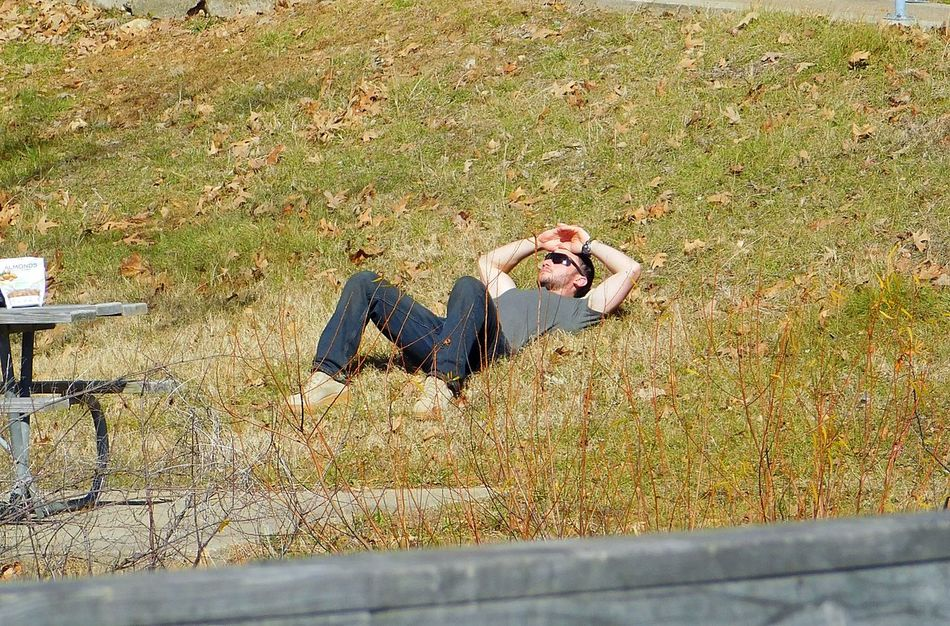 Man relaxing in the sunshine by the lake. Relaxing Enjoying Life People And Nature Lakeside Chilling Man Man Resting Soaking Up Sun Park Lake