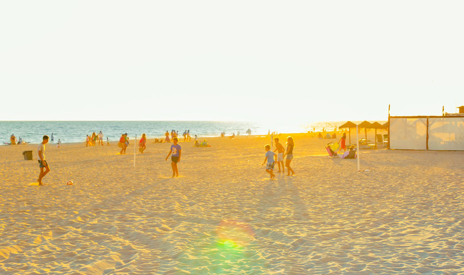 Summer in Spain. Young people playing on the beach at sunset. Rota, Cadiz. Beach Cadiz City Family Mediterranean  Men Ocean Ocean View Paradise People Promenade Relaxation Resort Rota Sand Sea SPAIN Summer Sunset Tourism Travel Destinations Vacations Walk Water Woman