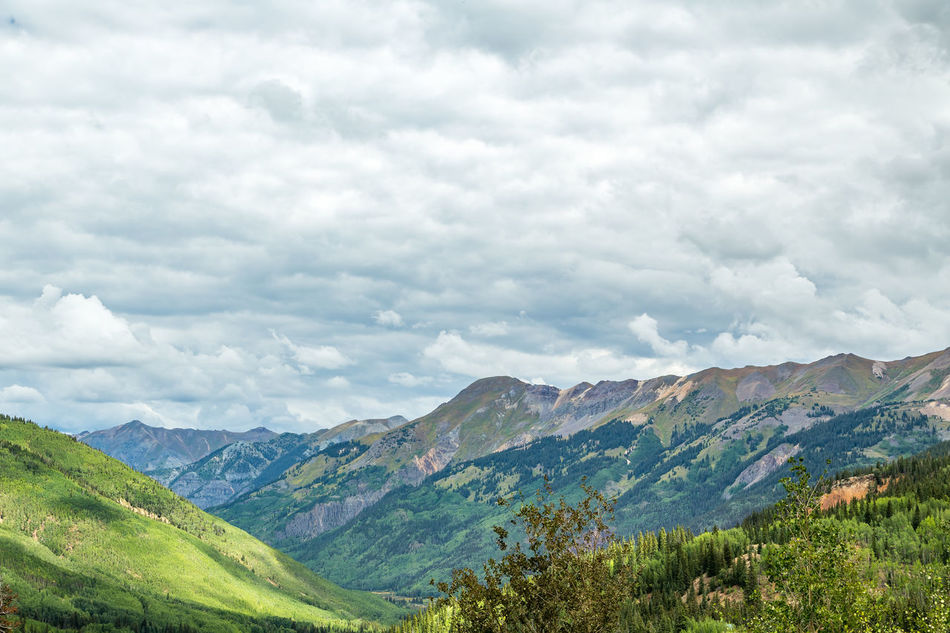 The San Juan Skyway forms a 233 mile loop in southwest Colorado traversing the heart of the San Juan Mountains festuring breathtaking mountain views and includes the portion of US 550 between Silverton and Ouray known as the Million Dollar Highway. Beauty In Nature Cloud - Sky Colorado Day Forest Landscape Lush - Description Million Dollar Highway Mountain Mountain Range Nature No People Outdoors Rockies Rocky Mountains San Juan Mountains San Juan Skyway Scenics Sky Southwest  Southwestern Usa