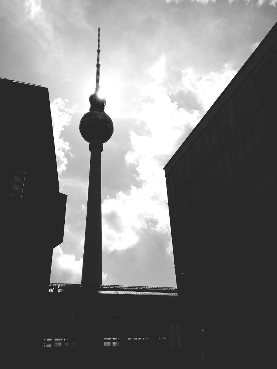 architecture, built structure, building exterior, low angle view, tall - high, tower, cloud - sky, sky, city, travel destinations, spire, communication, television tower, outdoors, no people, modern, day, silhouette, skyscraper