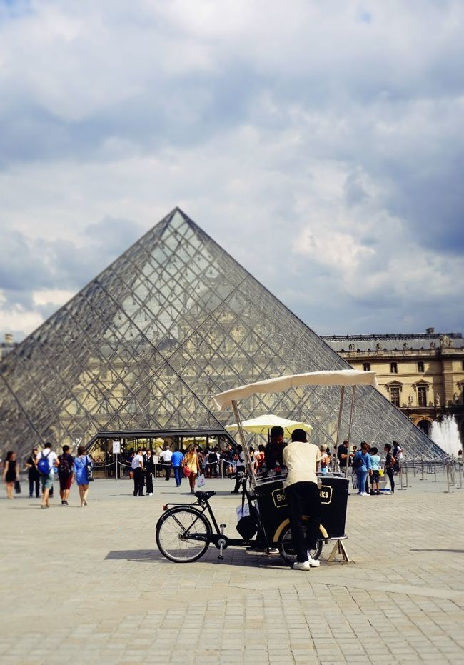 The Lourve Architecture Bicycle Built Structure Casual Clothing Cloud - Sky Famous Place International Landmark Lifestyles Lourve LourveMuseum Men Mode Of Transport People People Walking  Person Sky Tourism Tourist Tourists Transportation Travel Travel Destinations Tricycle Vacations People And Places.