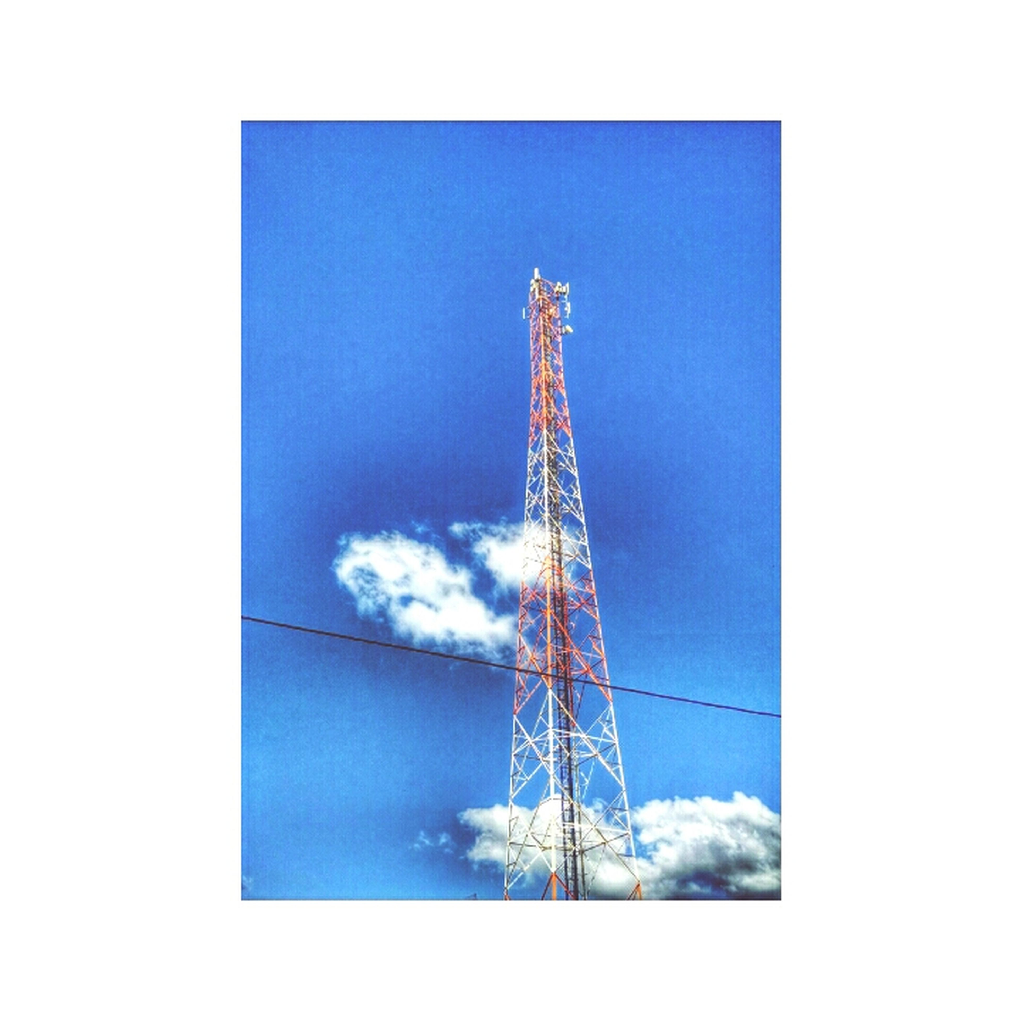 low angle view, transfer print, sky, electricity pylon, auto post production filter, fuel and power generation, power supply, technology, tall - high, electricity, power line, tower, cloud - sky, built structure, blue, connection, day, outdoors, tall, no people