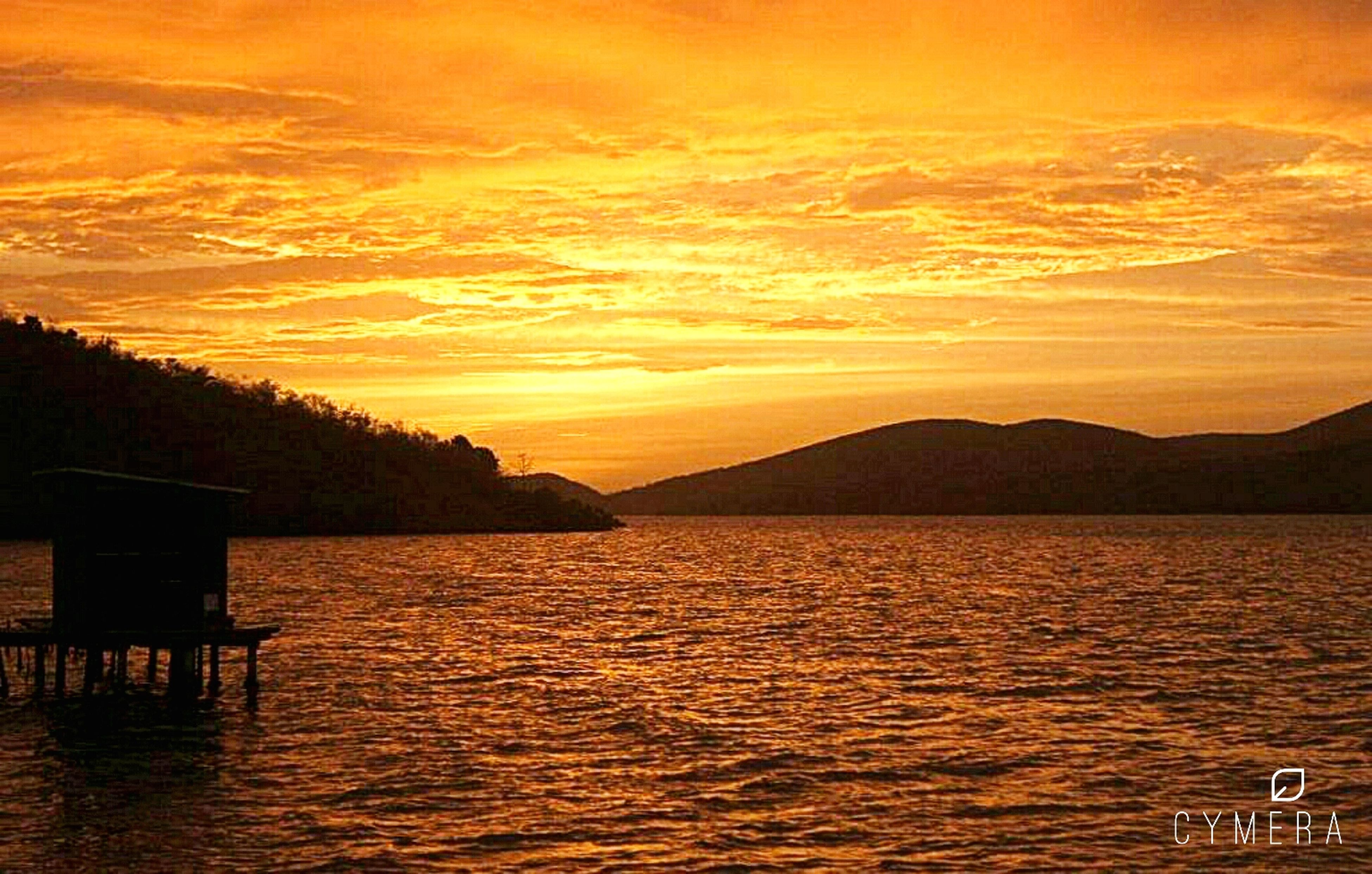 sunset, water, scenics, tranquil scene, tranquility, beauty in nature, silhouette, mountain, orange color, rippled, idyllic, nature, waterfront, sky, sea, lake, mountain range, non-urban scene, reflection, remote