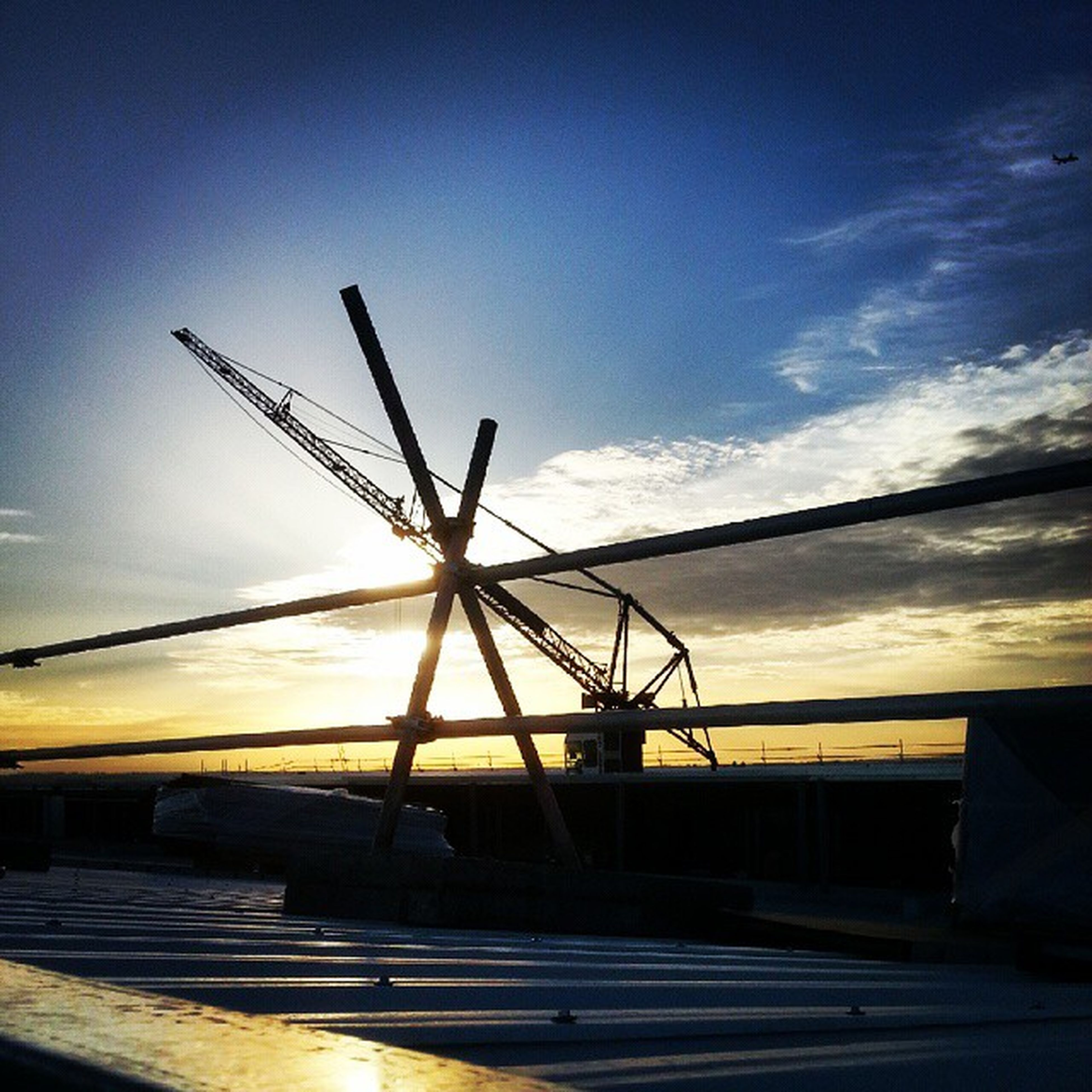 sky, sunset, transportation, crane - construction machinery, built structure, industry, mode of transport, silhouette, cloud - sky, construction site, development, architecture, outdoors, cloud, fuel and power generation, no people, dusk, low angle view, building exterior, freight transportation