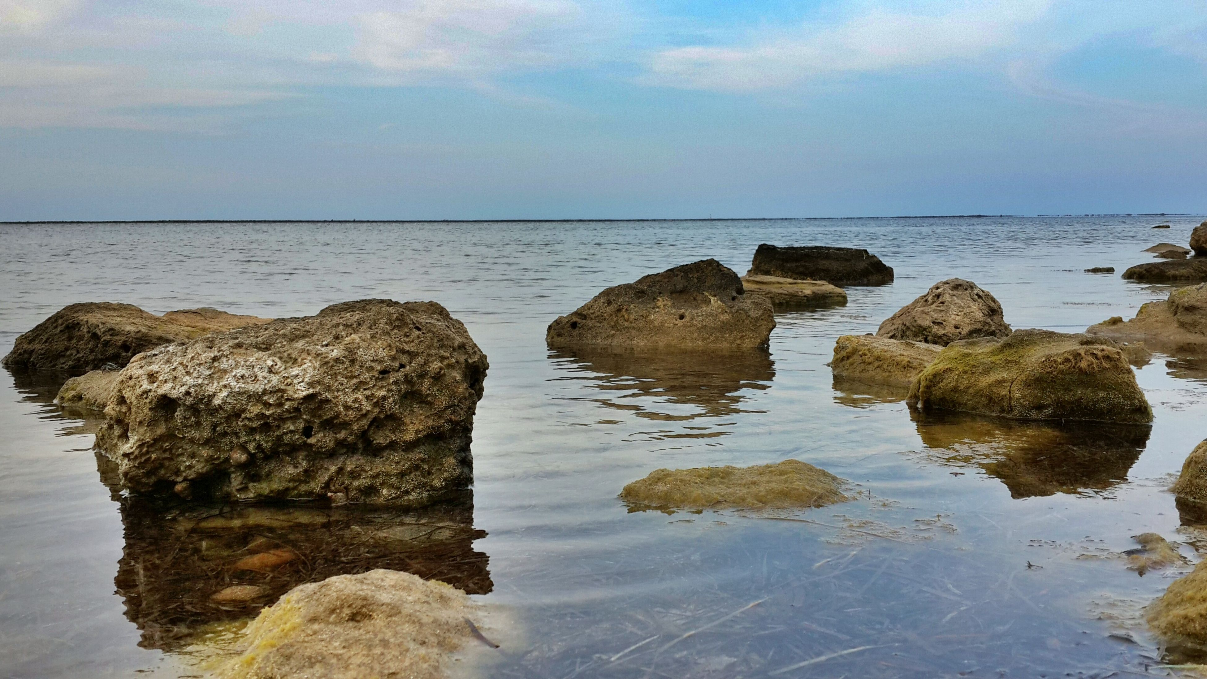 water, sea, horizon over water, tranquility, tranquil scene, sky, scenics, rock - object, beauty in nature, rock formation, nature, reflection, idyllic, rock, cloud - sky, cloud, waterfront, beach, shore, calm