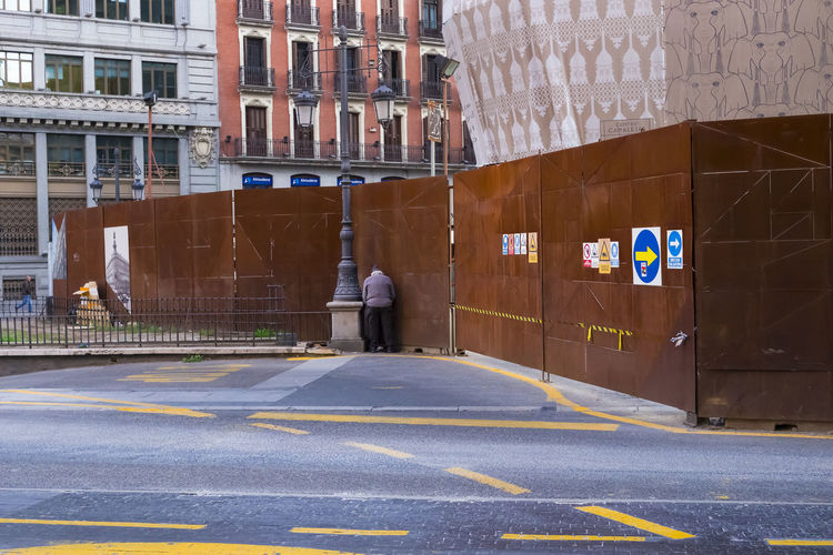 A candid street view of a man against the fence answering the call of nature of a building site in Madrid. City City Life City Street Funny Man View Wall Architecture Building Exterior Building Site Built Structure Call Of Nature Candid City City View  Day Editorial  Fence One Person Outdoors People Real People Road Road Marking Street