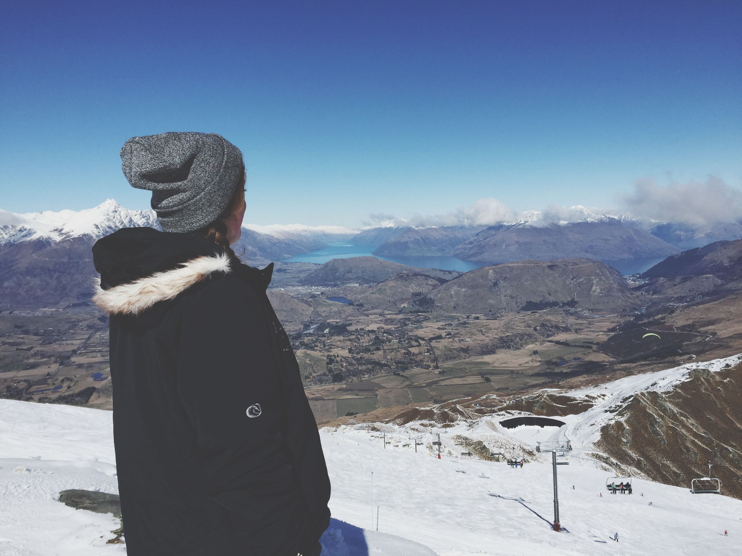 winter, snow, mountain, cold temperature, lifestyles, leisure activity, landscape, tranquil scene, standing, rear view, warm clothing, scenics, tranquility, sky, season, nature, mountain range, beauty in nature