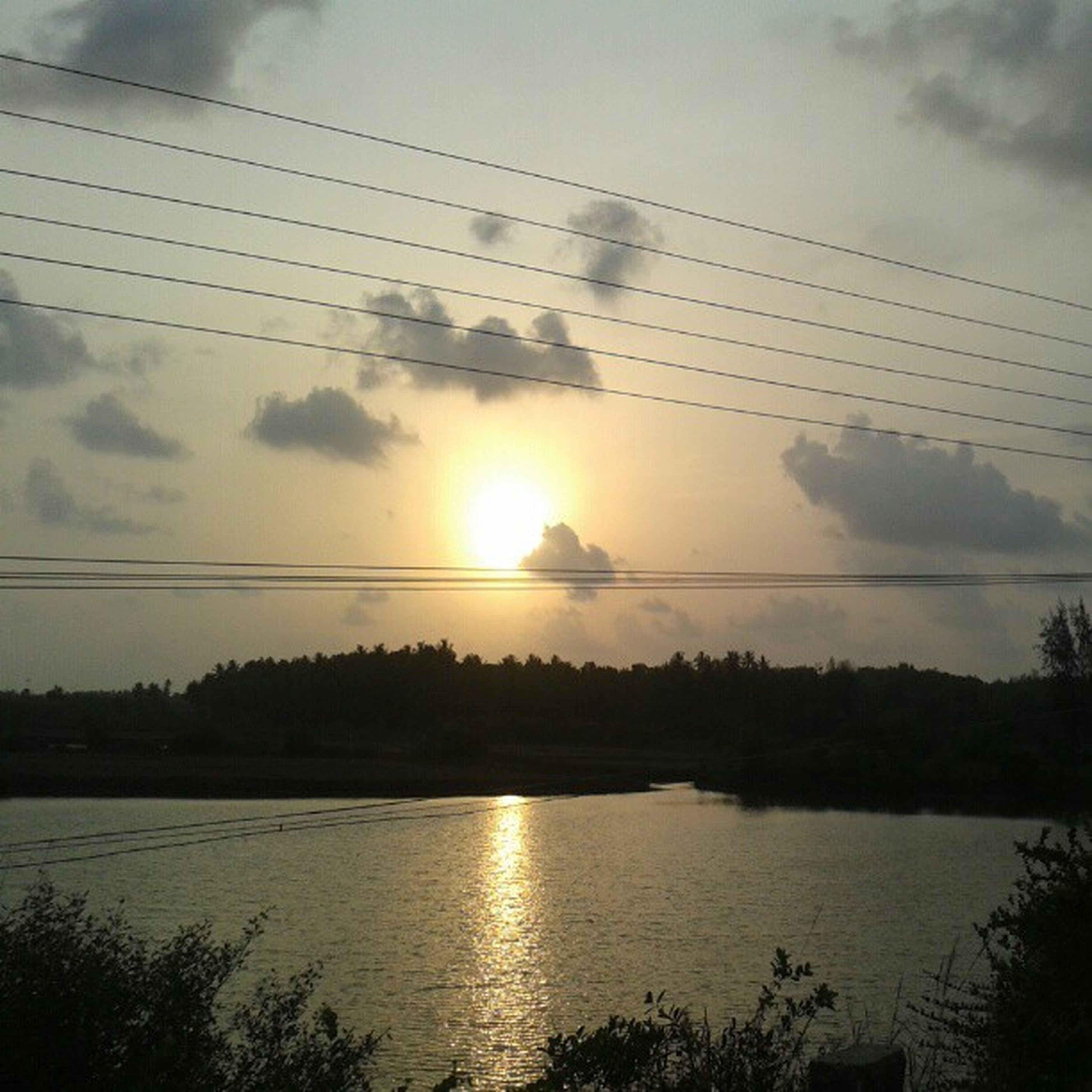 sunset, sky, water, tranquility, tranquil scene, sun, scenics, power line, reflection, beauty in nature, electricity pylon, cloud - sky, silhouette, nature, lake, cloud, idyllic, cable, sunlight, river