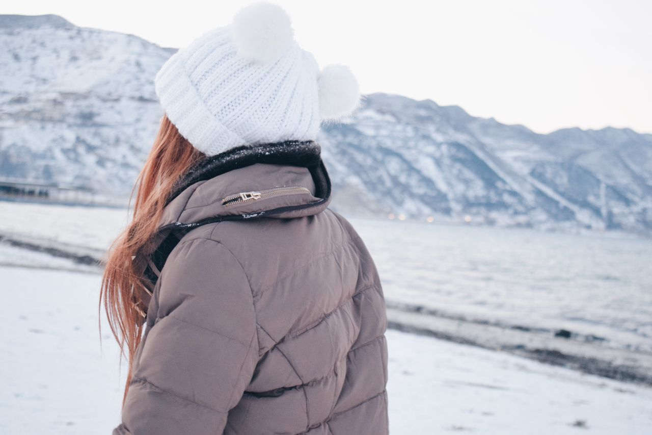 winter, rear view, cold temperature, snow, real people, warm clothing, leisure activity, knit hat, nature, one person, focus on foreground, outdoors, lifestyles, mountain, day, women, vacations, standing, beauty in nature, beach, sea, water, young women, young adult, close-up, people