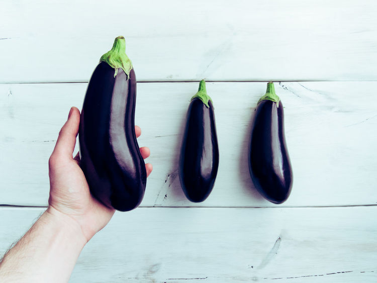 Male hand holding a fresh healthy eggplant, white wooden background. Agriculture Arranged Objects Aubergine Copy Space Diet Eggplant Fresh Gluten Free Healthy Lifestyle Kitchen Table Lines Minimalism Organic Food Organic Living Ripe Still Life Top View Of Food White Texture Wooden Texture