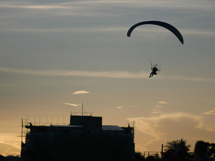 Flying Silhouette Wind Paragliding Extreme Sports People Parachute Multi Colored RISK Mid-air Sky Motion One Person Headwear Outdoors Stunt Person Pilot Urban Skyline City Day Live For The Story The Great Outdoors - 2017 EyeEm Awards The Photojournalist - 2017 EyeEm Awards EyeEmNewHere