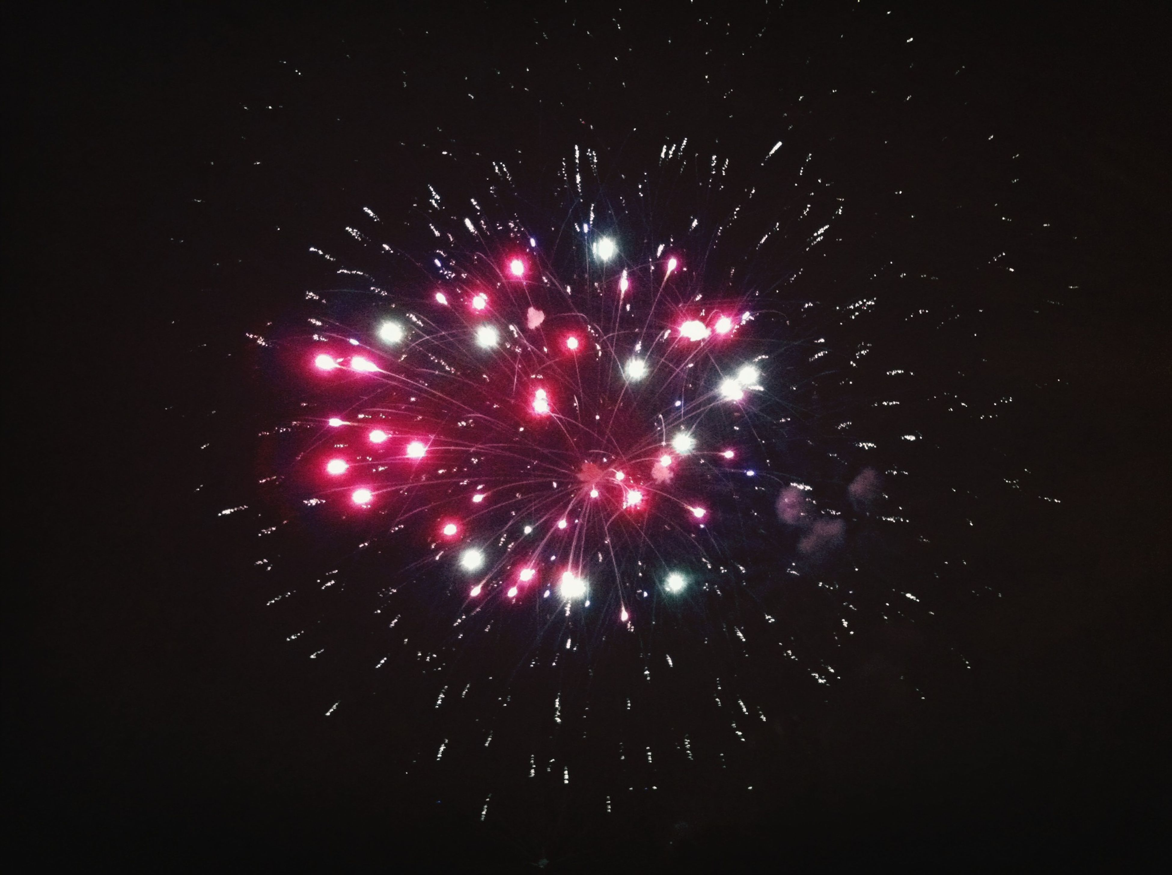 night, celebration, illuminated, firework display, low angle view, exploding, glowing, long exposure, firework - man made object, motion, event, firework, red, arts culture and entertainment, sparks, dark, sky, entertainment, celebration event, no people