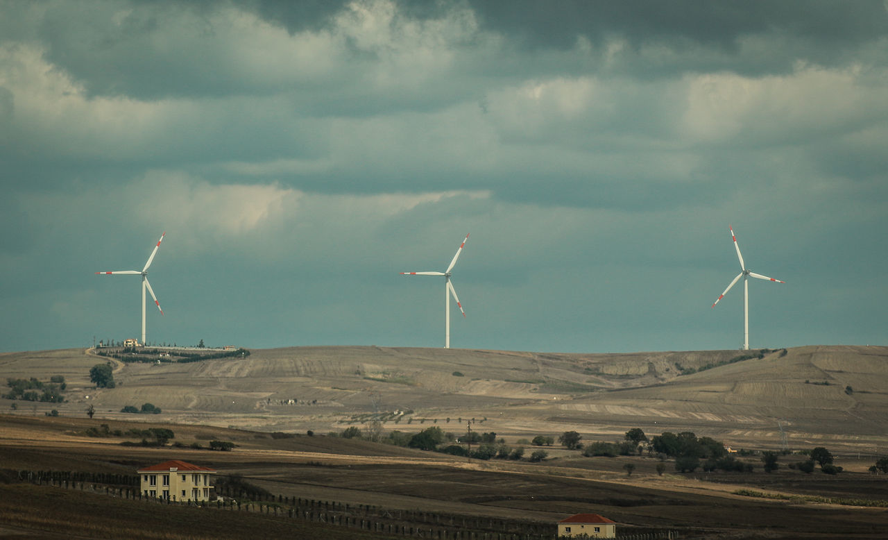 Windmills On Field Against Cloudy Sky