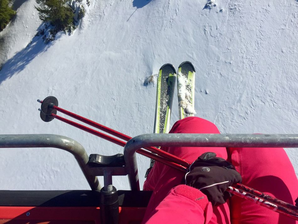 View from above of woman skier in the teleski wearing gloves and holding ski poles Outdoors Day One Person Adult People Woman Teleski Skilift Winter Snow Slope Feet Legs Skier Hands Hold Skipoles Gloves Mountains Air Transport Topview Skiing
