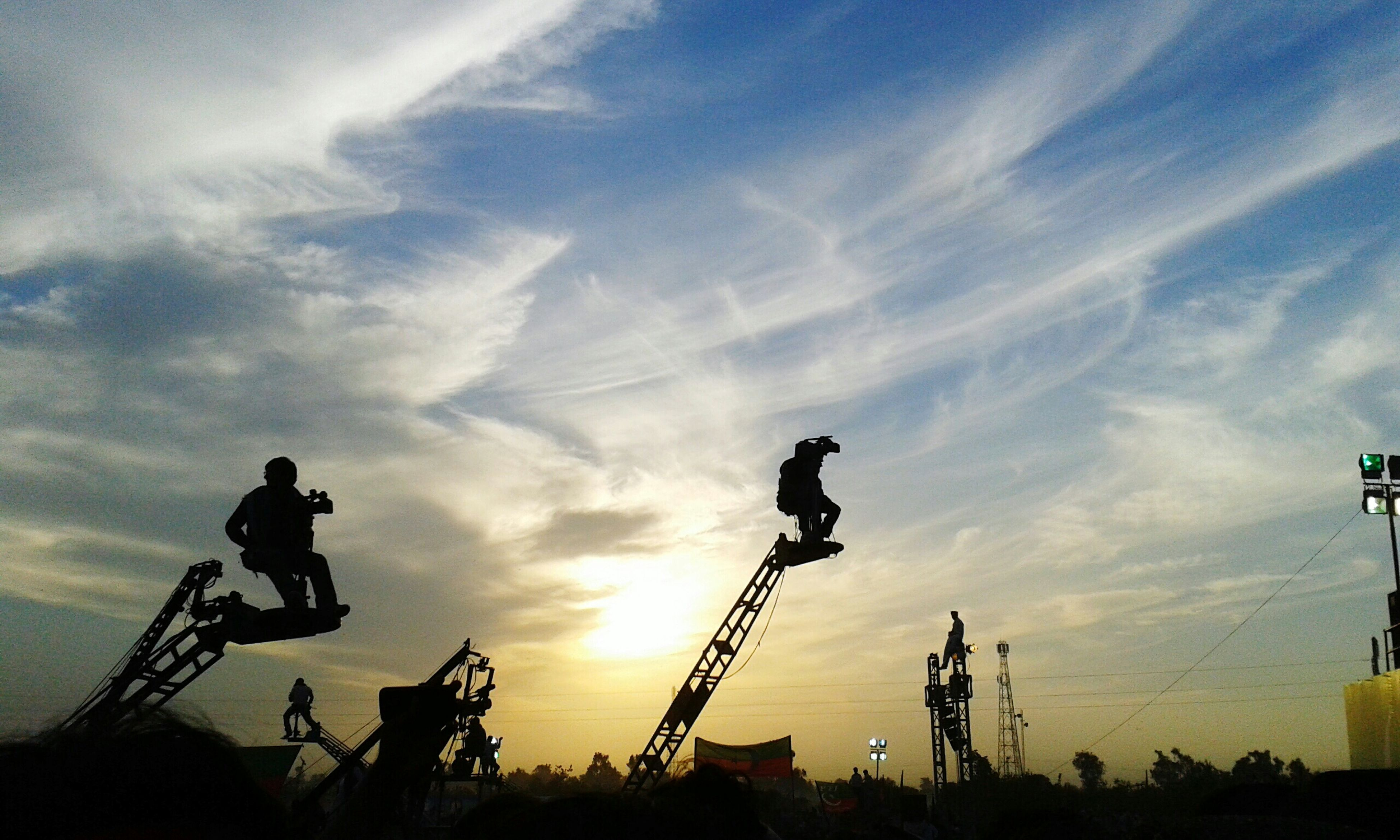 sky, silhouette, low angle view, sunset, cloud - sky, leisure activity, men, lifestyles, cloud, bicycle, outdoors, technology, sunlight, street light, nature, full length, cloudy