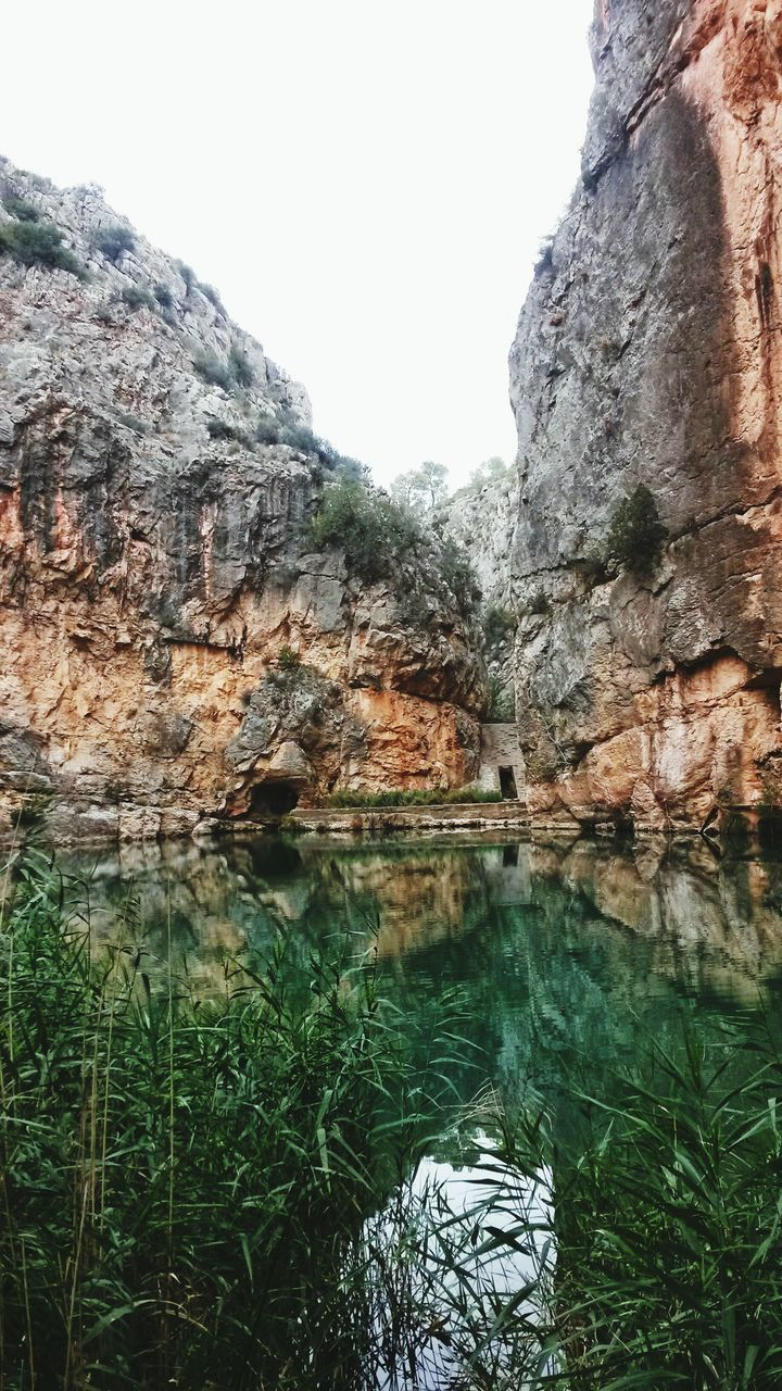 rock - object, rock formation, nature, geology, physical geography, day, tranquility, beauty in nature, tranquil scene, scenics, outdoors, cliff, no people, water, cave, adventure, tree, grass, rock face, sky