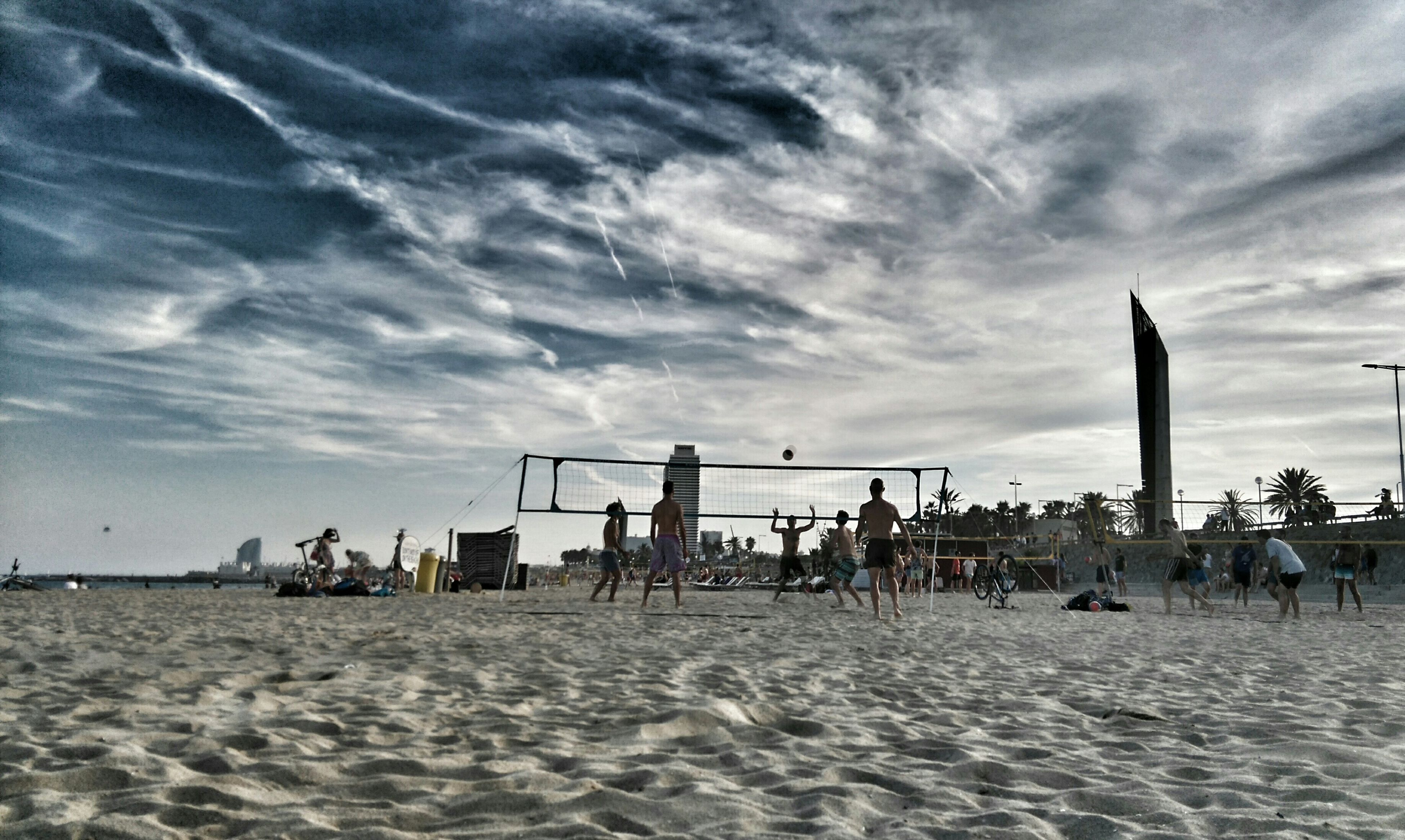 beach, sea, sand, sky, cloud - sky, large group of people, shore, water, vacations, built structure, incidental people, cloudy, horizon over water, cloud, scenics, mixed age range, nature, leisure activity, tourism