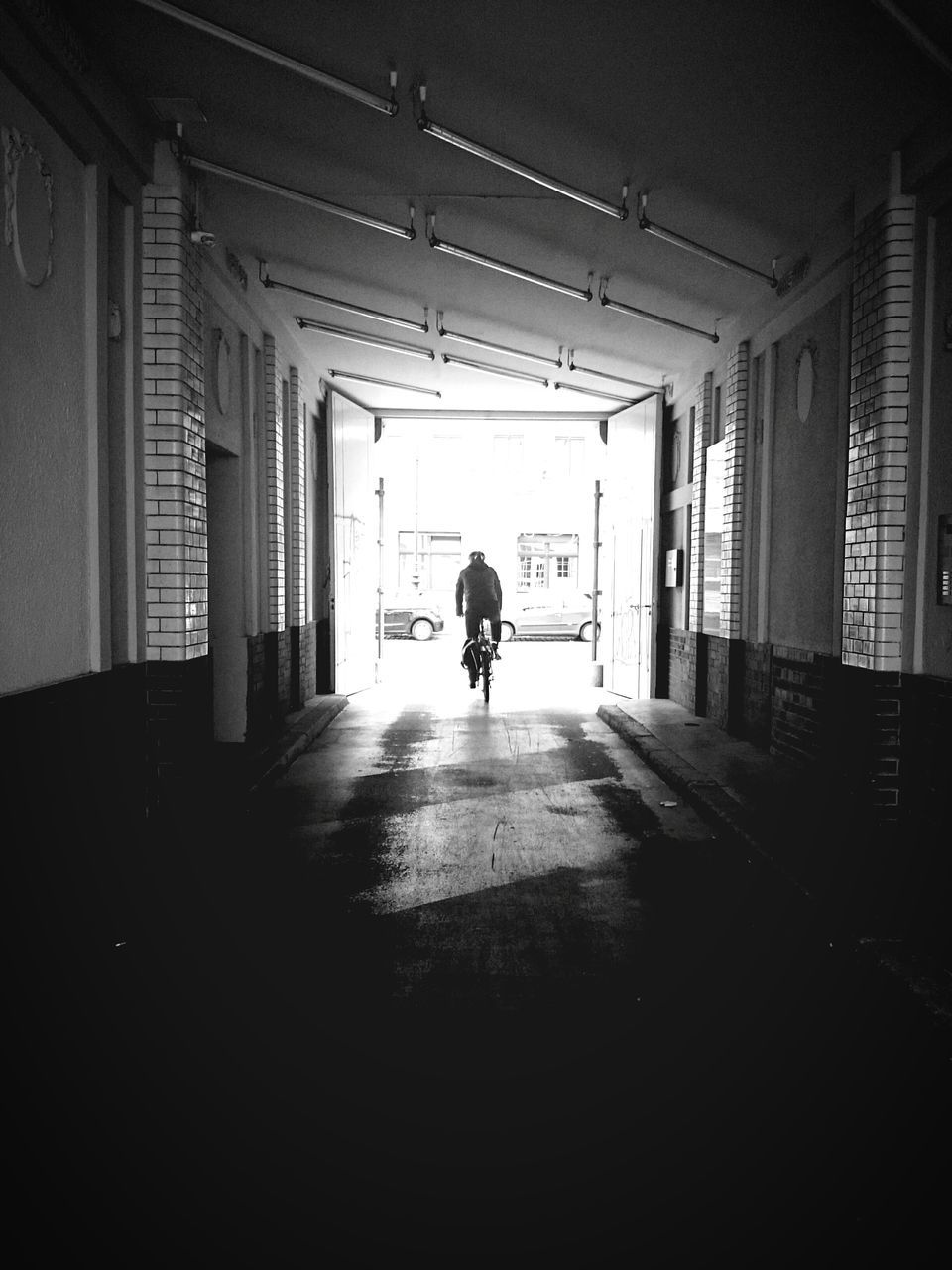 Man Riding Bicycle On Footpath Amidst Buildings