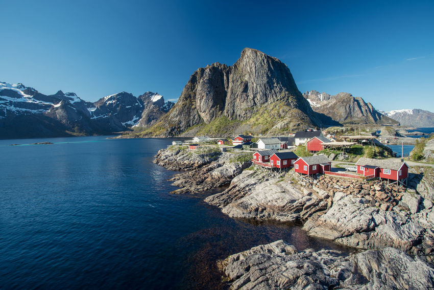 Classic view of red fishing huts against fjord and mountains in Hamnoy, Lofoten, Norway Fishing Hut Red Day Hamnøy Lofoten Norway Summer Sun Clear Sky Scenics Beauty In Nature Nature Tranquil Scene No People Outdoors Travel Destinations Landscape Ocean Mountain Mountain Range Tranquility Water Sky Rock - Object Idyllic Sea Mode Of Transport Waterfront Blue