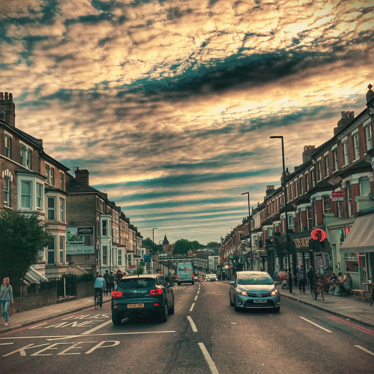 car, street, architecture, land vehicle, transportation, city, building exterior, road, sky, built structure, cloud - sky, mode of transport, outdoors, sunset, no people, day