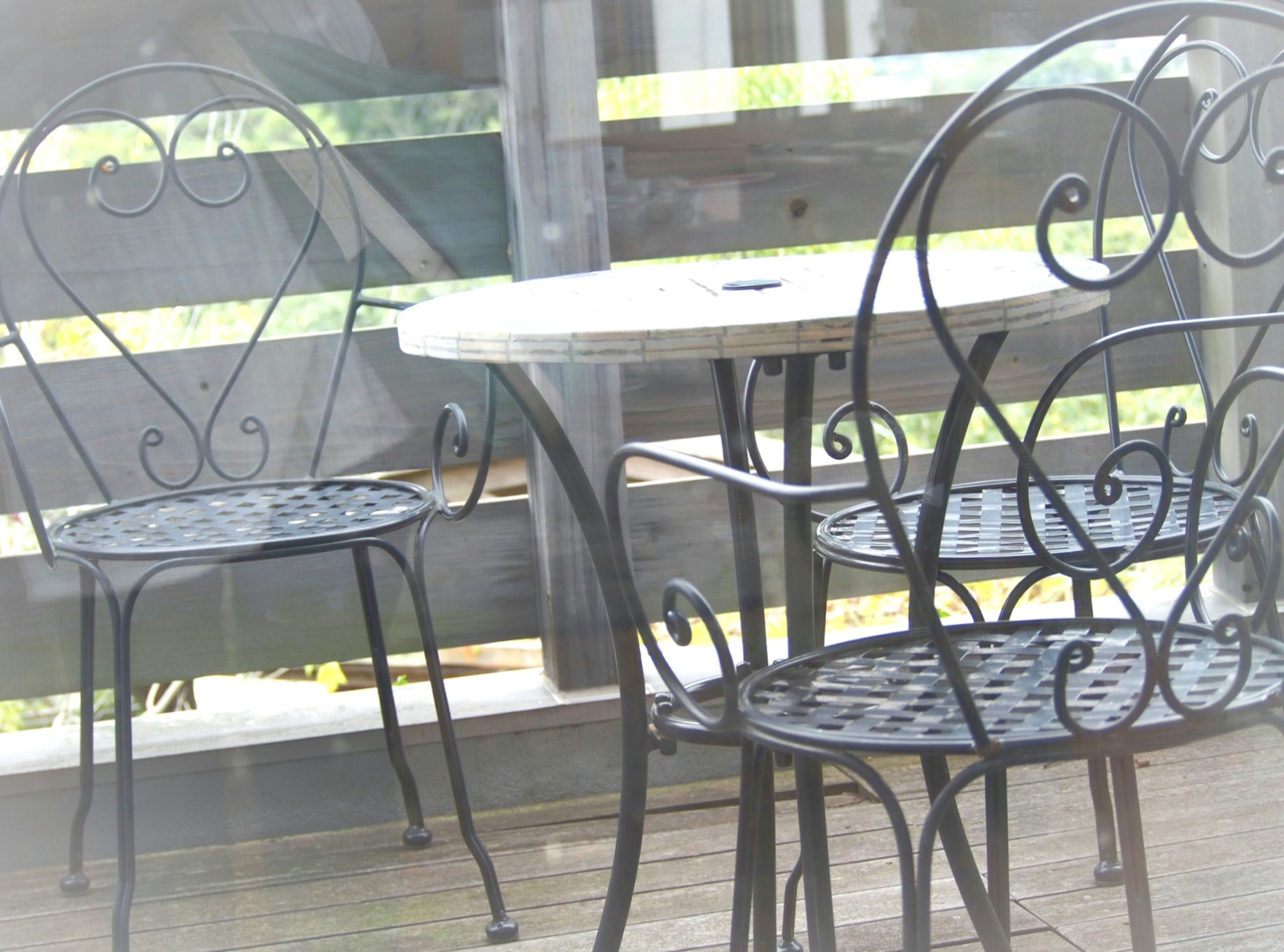 chair, empty, indoors, absence, seat, table, window, flooring, restaurant, in a row, group of objects, wrought iron, order, patio