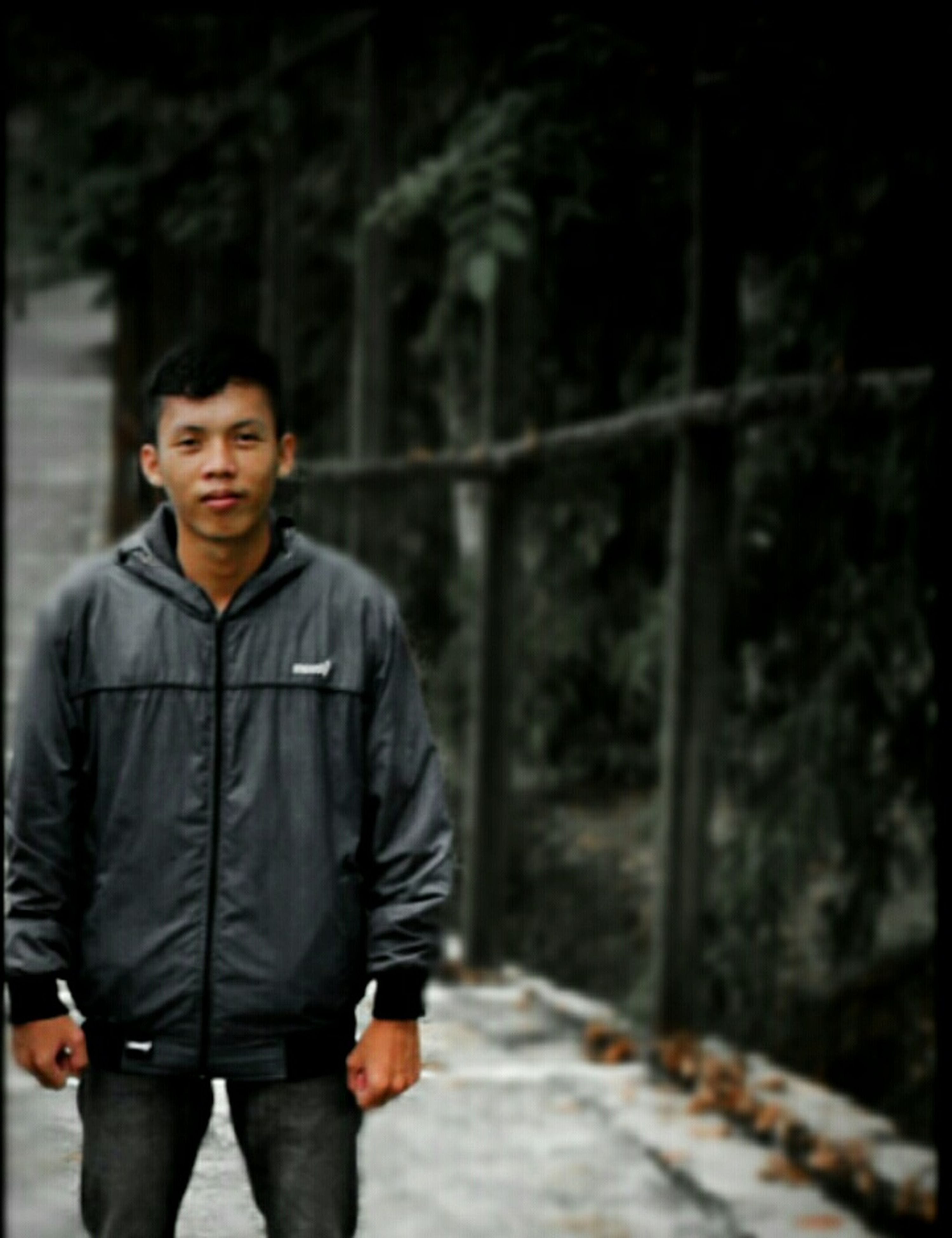 casual clothing, lifestyles, standing, leisure activity, full length, warm clothing, jacket, looking at camera, hands in pockets, front view, portrait, person, walking, young men, rear view, tree, focus on foreground, young adult