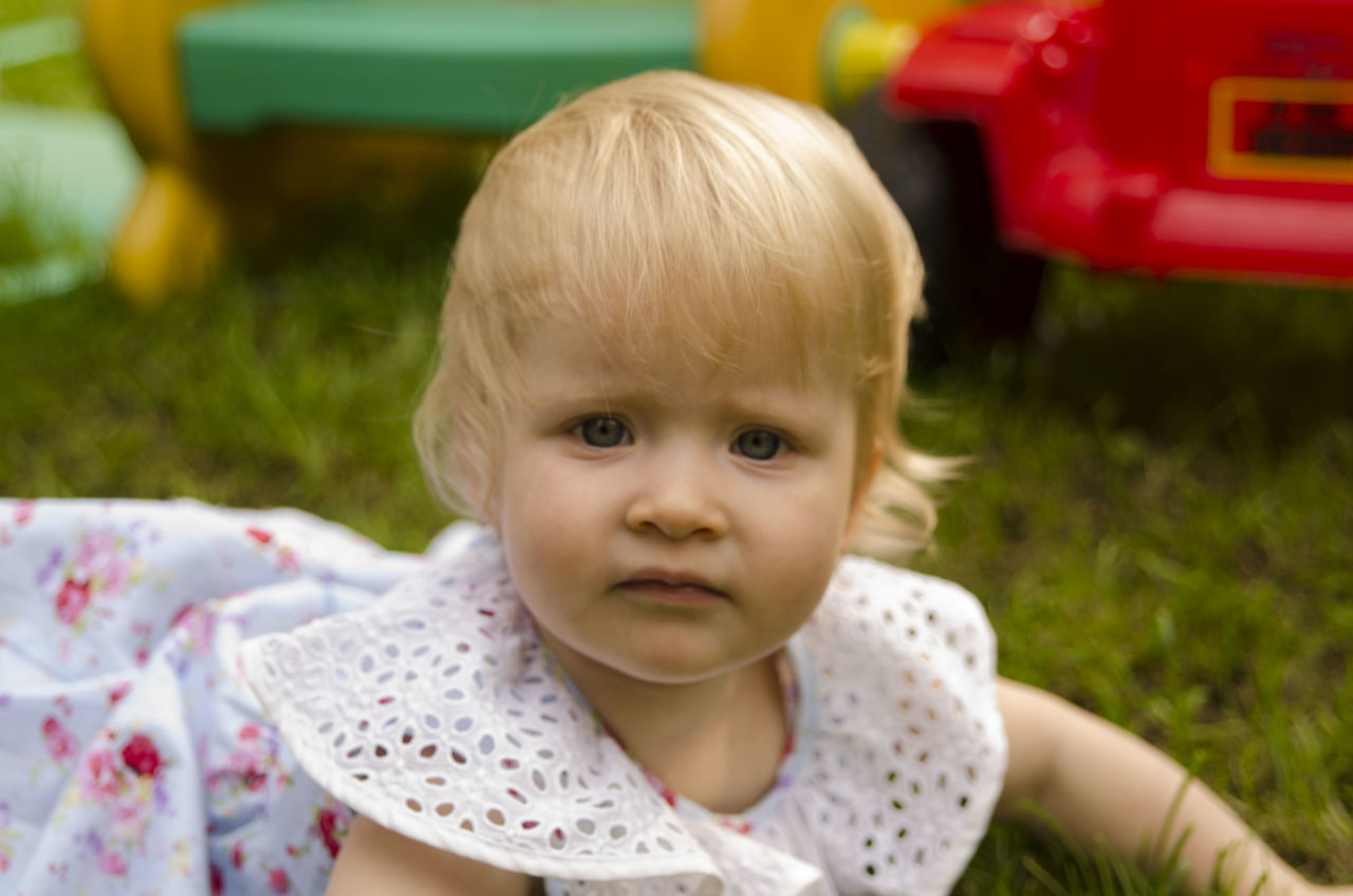 childhood, real people, one person, cute, day, close-up, looking at camera, portrait, outdoors, blond hair, grass, people