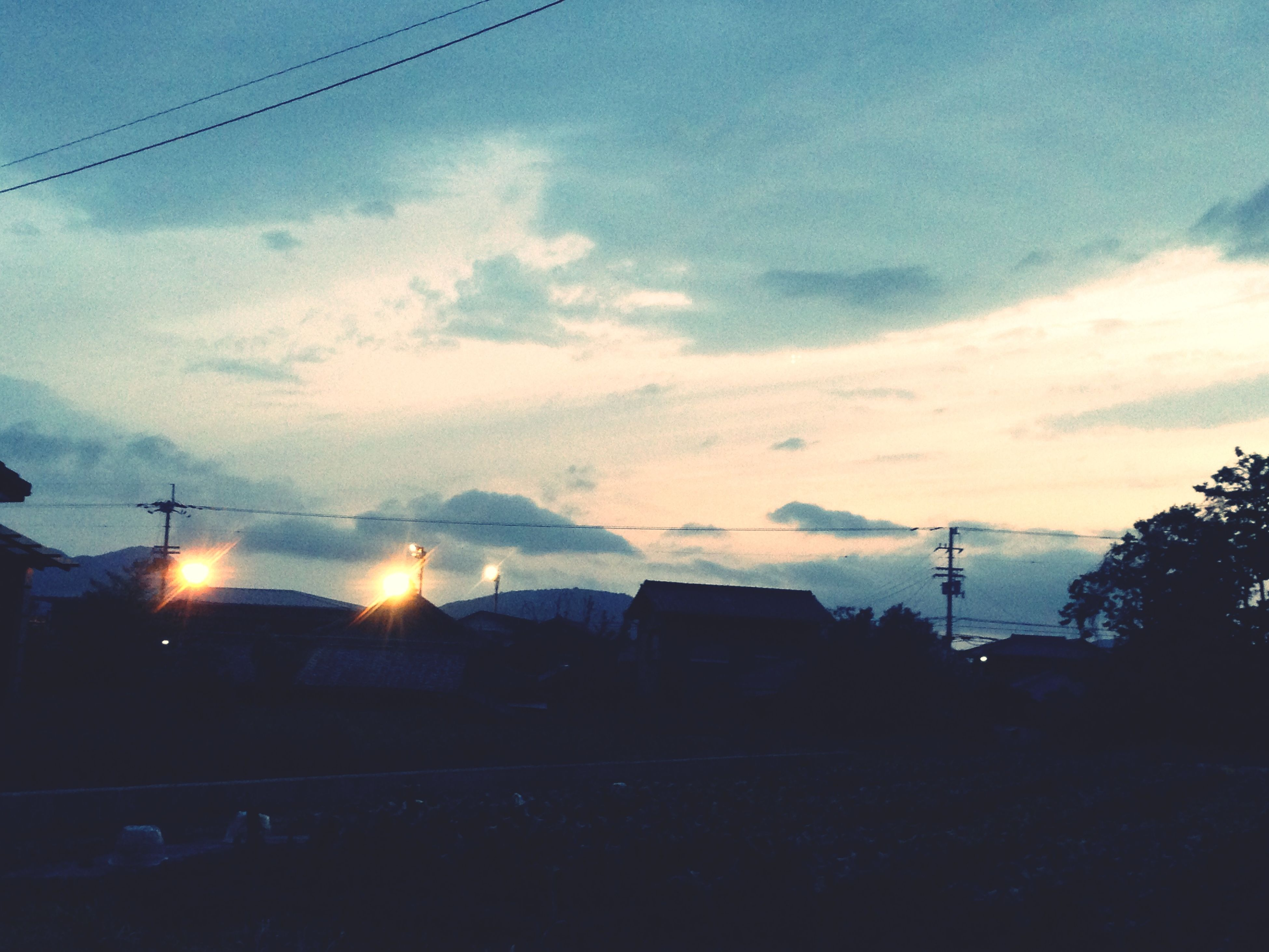 power line, sky, electricity pylon, building exterior, silhouette, electricity, built structure, architecture, cable, power supply, cloud - sky, sunset, house, low angle view, fuel and power generation, connection, cloud, power cable, tree, dusk