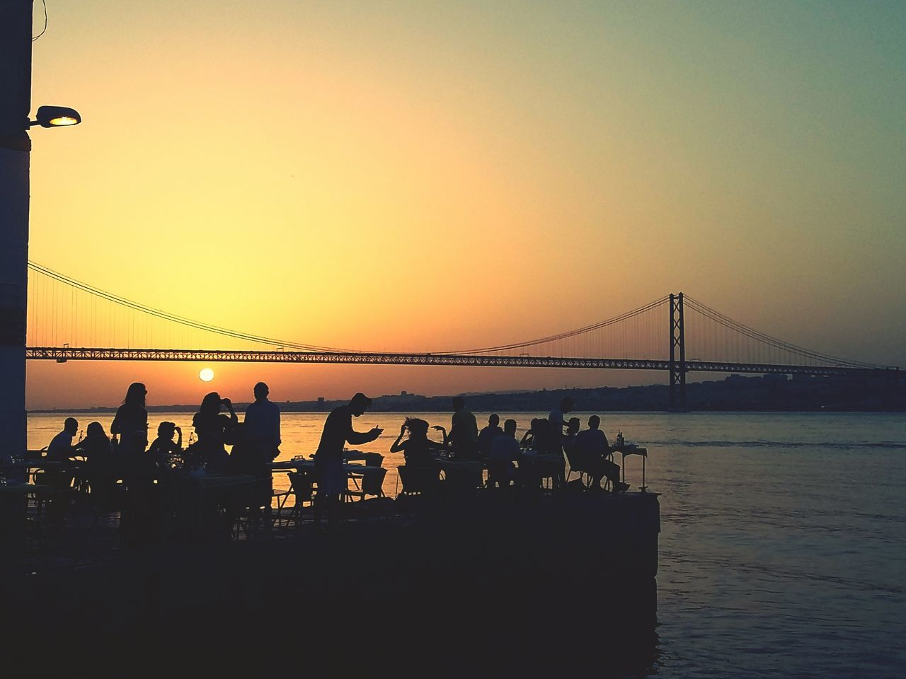 sunset, silhouette, water, sea, bridge - man made structure, suspension bridge, connection, nature, sky, clear sky, bridge, built structure, lifestyles, architecture, men, beauty in nature, outdoors, real people, large group of people, beach, scenics, travel destinations, horizon over water, day, people