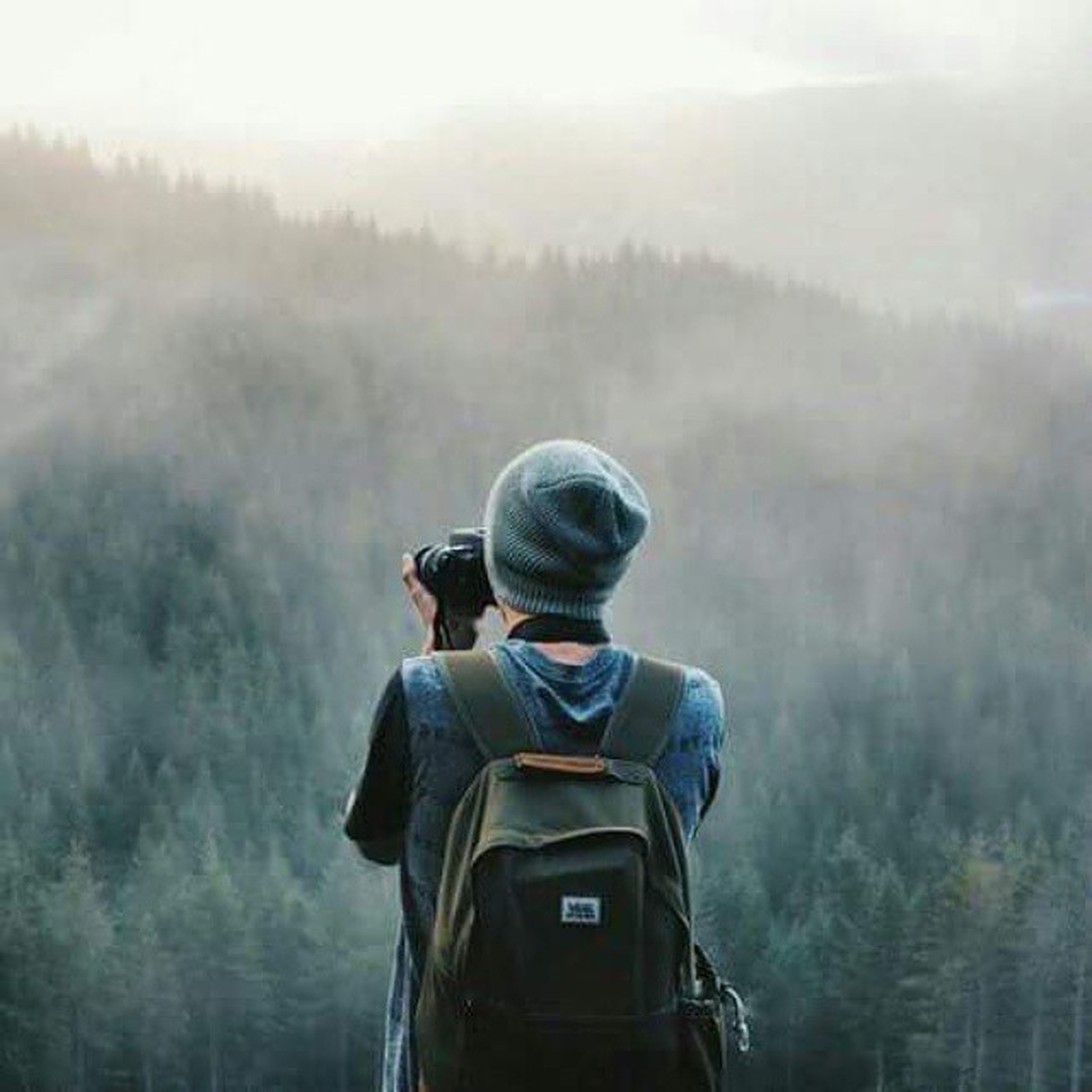 lifestyles, photography themes, leisure activity, photographing, camera - photographic equipment, rear view, technology, sitting, men, holding, digital camera, wireless technology, casual clothing, waist up, focus on foreground, three quarter length, photographer, hobbies
