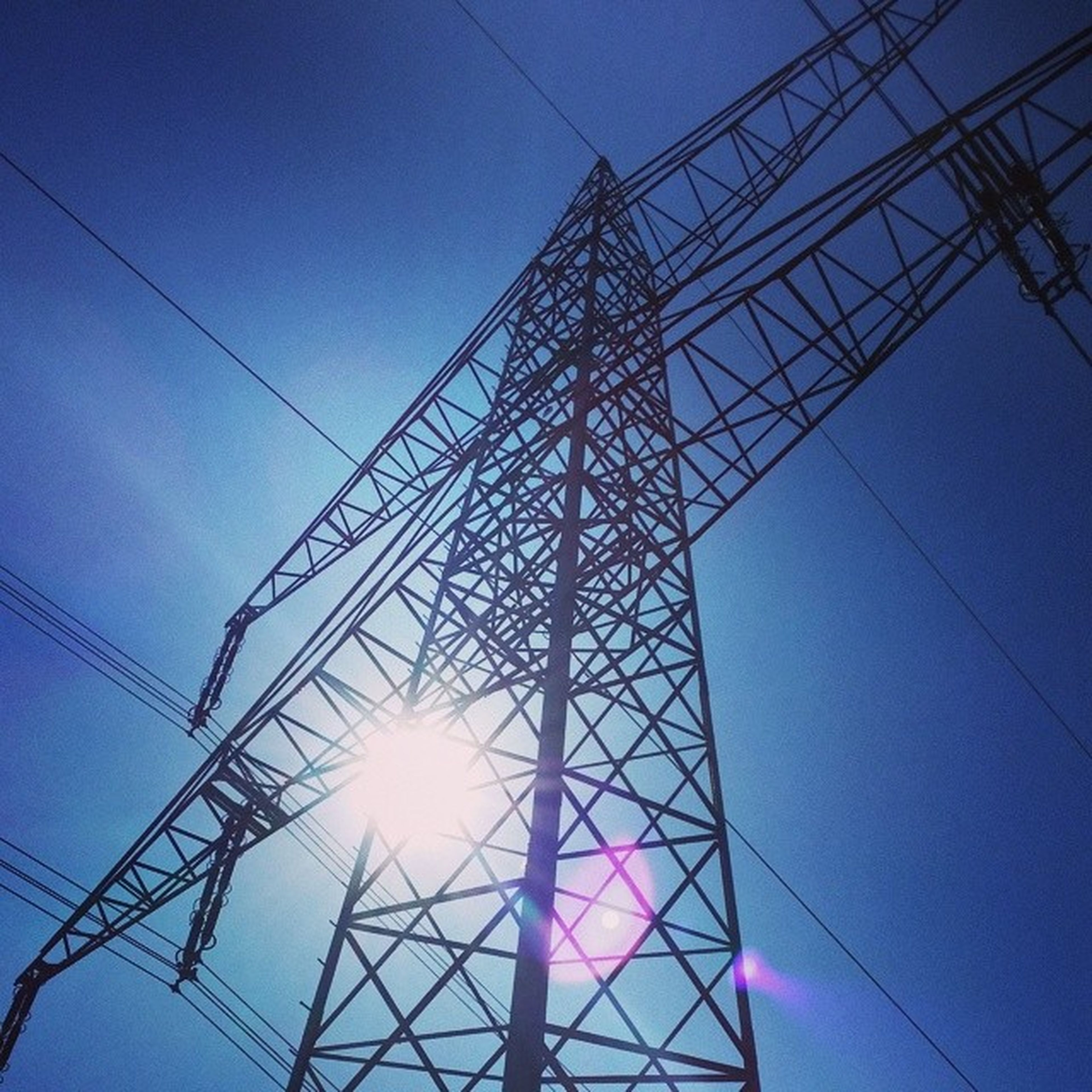 low angle view, power line, electricity, electricity pylon, power supply, connection, fuel and power generation, cable, technology, blue, sky, silhouette, power cable, complexity, sun, clear sky, sunlight, no people, outdoors, lighting equipment