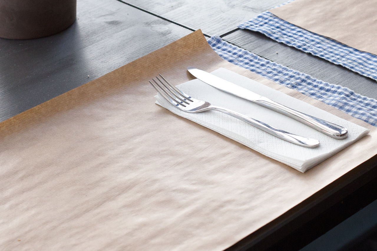 High Angle View Of Cutlery With Tissue And Paper Arranged On Table