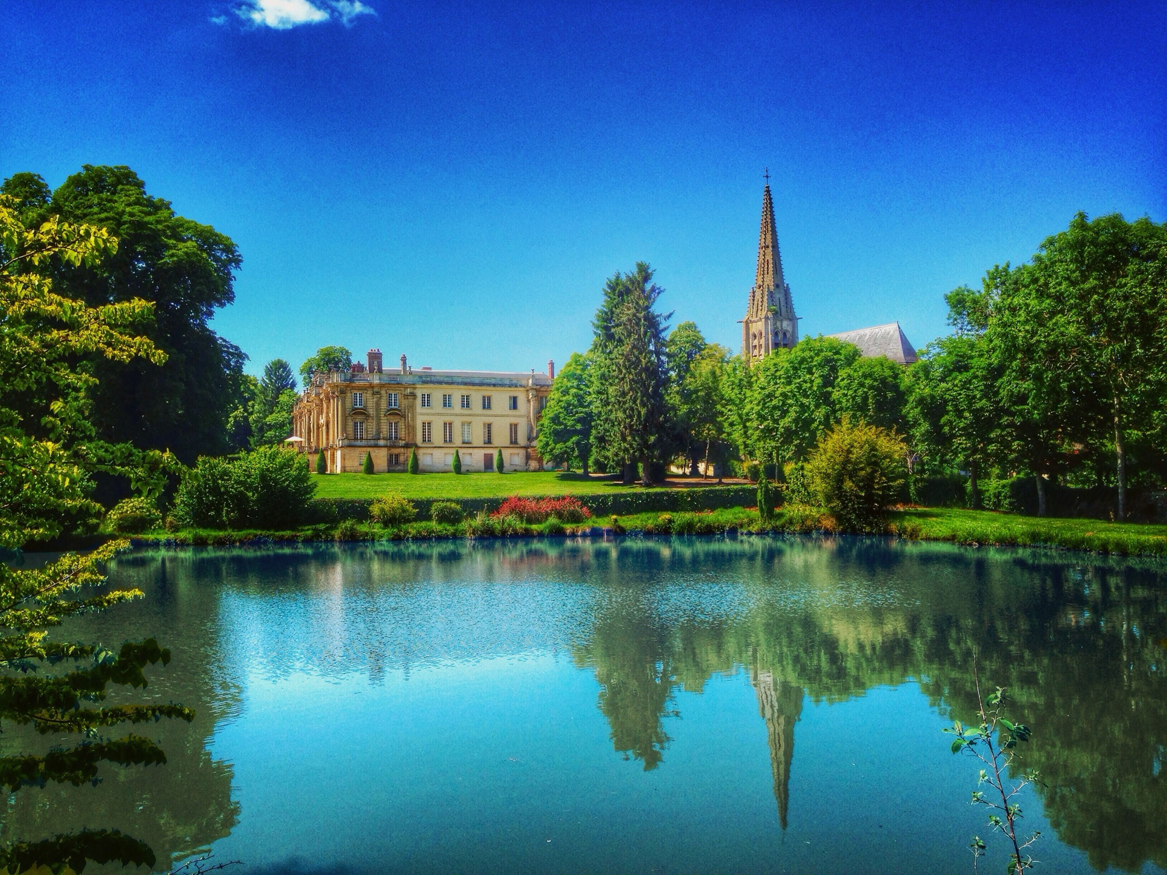 architecture, building exterior, built structure, reflection, tree, water, blue, waterfront, clear sky, lake, pond, sky, standing water, travel destinations, religion, famous place, tower, outdoors, river, place of worship