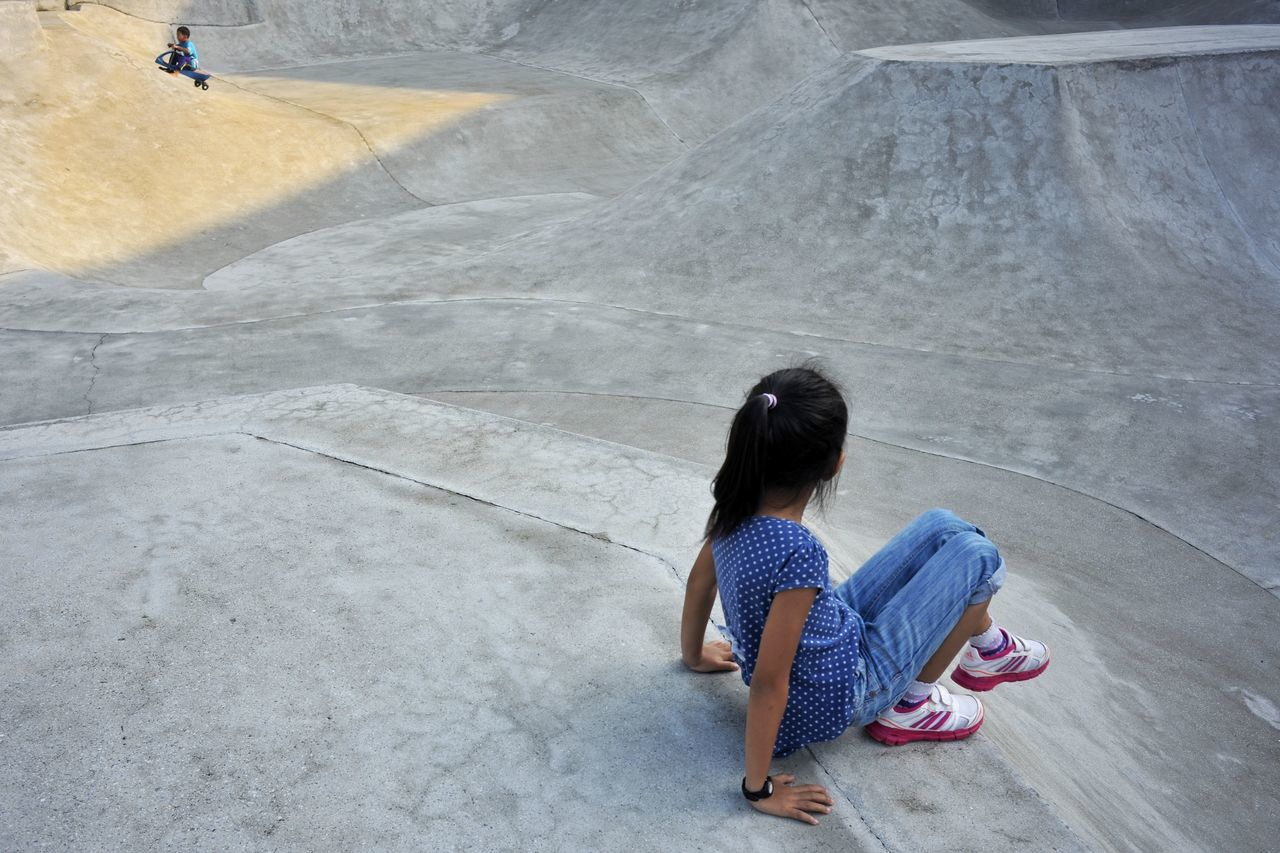 full length, one person, real people, sitting, high angle view, casual clothing, day, outdoors, childhood, skateboard park, people, adult