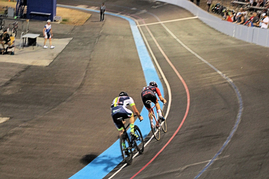"Are the bicycles ridden at the Velodrome different from a normal street bicycle? Absolutely. They are fixed-gear bikes with NO brakes. A fixed-gear bicycle (or fixed-wheel bicycle, commonly known in some places as a fixie) is a bicycle that has a drivetrain with no freewheel mechanism—think: no coasting—that's ridden without brakes. A fixed gear bike can be ridden marginally safely because the pedals are locked to the rear wheel in both directions, so locking up your legs can slow down the rear wheel. This means that when the back wheel turns, the pedals are always turning. A track bike has no brakes because braking would cause a pile up. Don't ask me more than that about these bikes. I have watched them, I have read about them, and I have talked with riders and I still don't understand it; but they make it work and it is a fun sport to watch. Where to next in this Series entitled ""... need for speed?"" Helmet, Racers, Track, Balboa Park, Morley Field, San Diego, California, Velodrome, Bicycle Racing, Fixed Gear Bike, Bicycle, Riders, Oval Track, San Diego, California, Balboa Park, Morley Field, Evening, Night,"