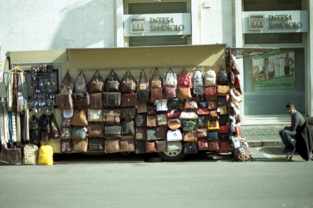 A guy selling a bunch of bags Analogue Photography Bags Business Guy Italy Nikon Fm2 Outdoors Rome Seller Small Shop