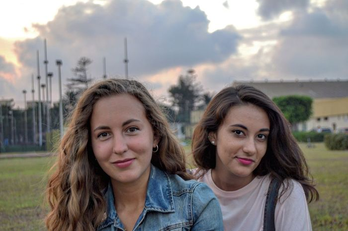 People And Placeshappy friends Young Women Togetherness Portrait Young Adult Looking At Camera Friendship Focus On Foreground Leisure Activity Smiling Front View Happiness Toothy Smile Lifestyles Field Headshot Bonding Person Long Hair Day Sky