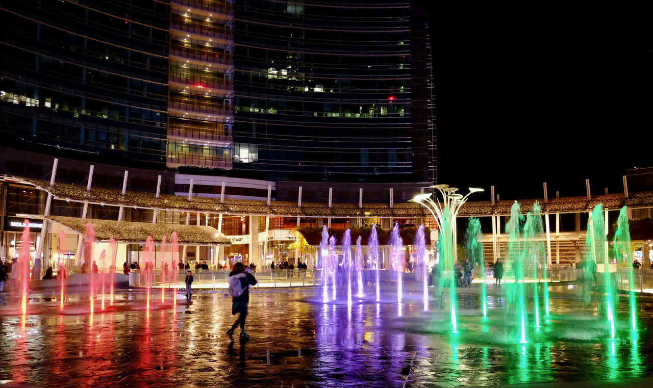Architecture Building Exterior Built Structure City Fountain Full Length Illuminated Leisure Activity Lifestyles Men Modern Motion Nature Night One Person Outdoors People Real People Reflection Sky Travel Destinations Walking Water Waterfront Women