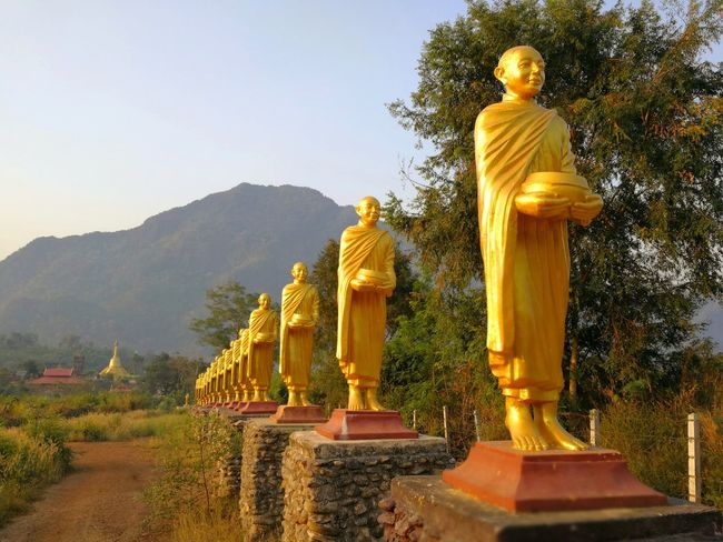 Statues of buddhist monks along the road to temple. Statue Monks Temple Buddha YellowsSacred Belive Village Color Thailand Rural Countryside Road City Beatiful Building Art Mountain Tree Shadow Light