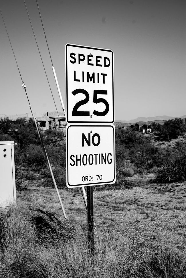 Speed limit sign with No Shooting sign as seen in Arizona. Black And White Forbidden No People No Shooting Sign Road Sign Speed Limit 25 Speed Limit Sign Text Warning Sign