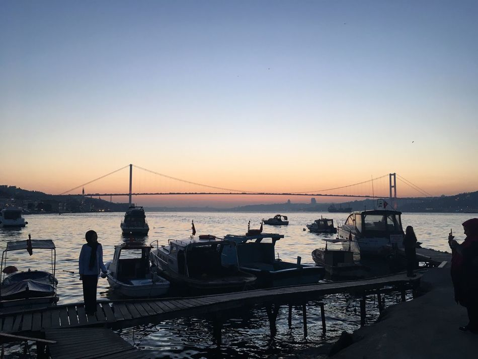 Miles Away Water Sea Transportation Sunset Mode Of Transport Nautical Vessel Clear Sky Sky Men Real People Nature Outdoors Moored Scenics Standing Women Connection Horizon Over Water Bridge - Man Made Structure Architecture The City Light