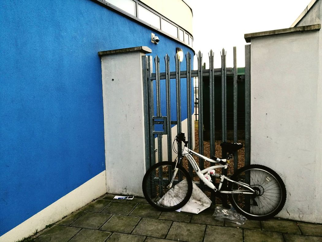 Blue Bicycle Architecture Built Structure No People Clear Sky Building Exterior Outdoors Day Sky Color Explosion Minimalist Architecture Huawei P9 Leica Metal Huaweiphotography Communication White And Blue Colour A white bicycle by gate to a blue building in London, today photo.