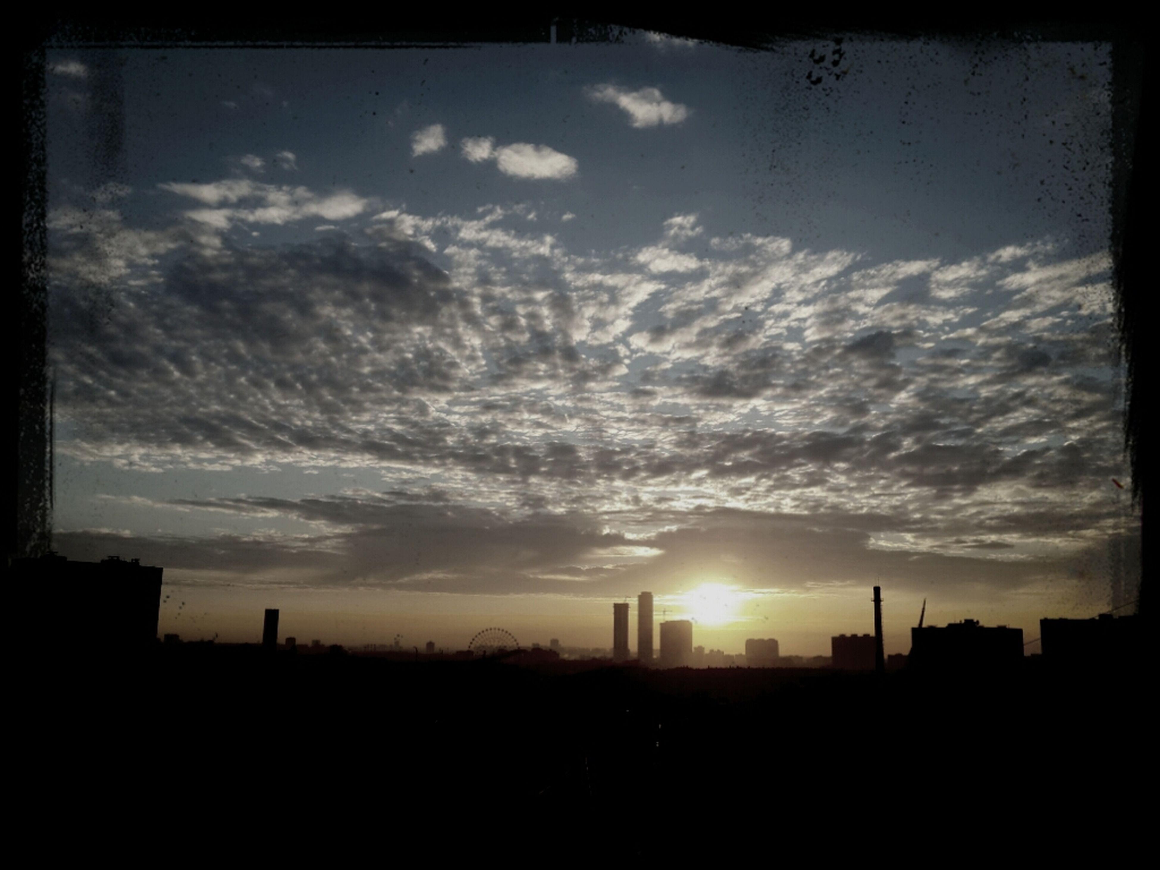 silhouette, sunset, building exterior, sky, architecture, built structure, cloud - sky, city, cloudy, cityscape, cloud, sun, dark, beauty in nature, scenics, urban skyline, nature, outdoors, sunlight, no people