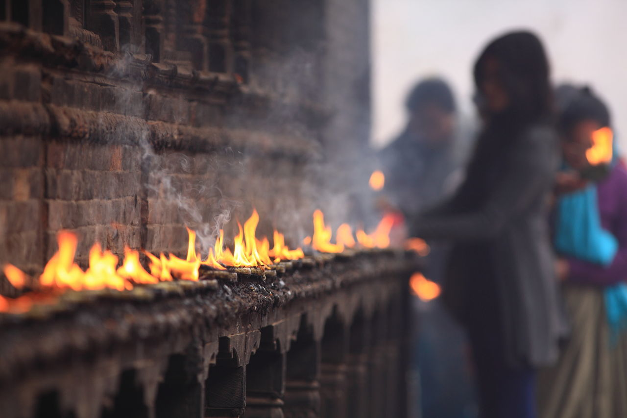 People Burning Candles At Temple